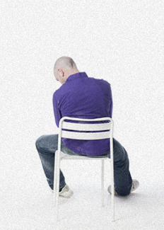 Depressed man hunched in chair, facing away and staring at the floor